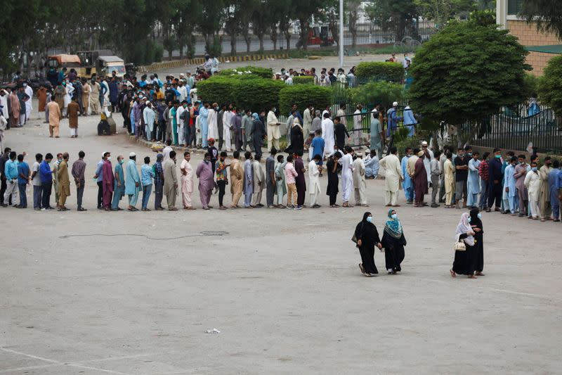 Residents line up to receive a vaccine against COVID-19 at a vaccination facility in Karachi