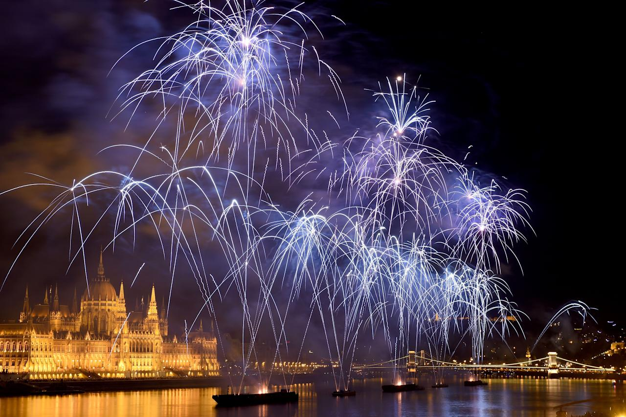 <p>Fireworks burst by the Hungarian Parliament building and the oldest Hungarian Bridge the 'Lanchid' (Chain Bridge) crossing the Danube River in Budapest on August 20, 2018 during the celebration of Hungary's national day. – Hungary marks the 1,018th anniversary of the foundation of the Hungarian state, established by the first king of Hungary, Stephen I. (Photo by ATTILA KISBENEDEK/AFP/Getty Images) </p>