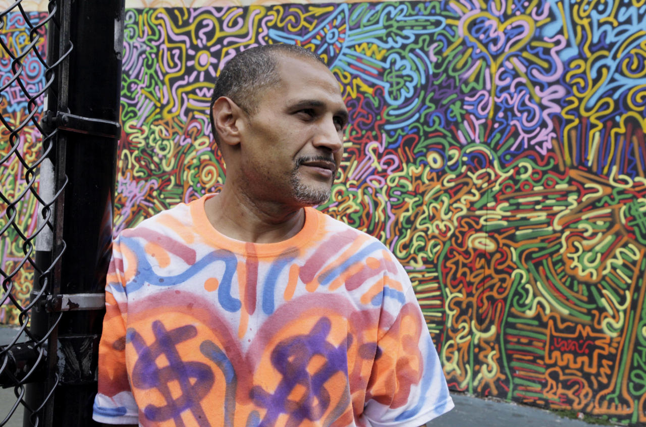 """In this Friday, July 27, 2012 photo, graffiti artist Angel """"LA II"""" Ortiz poses for photos with one of his creations, in a schoolyard on New York's Lower East Side. A number of New York's graffiti artists of the 1970s and '80s still have the urge to tag. (AP Photo/Richard Drew)"""
