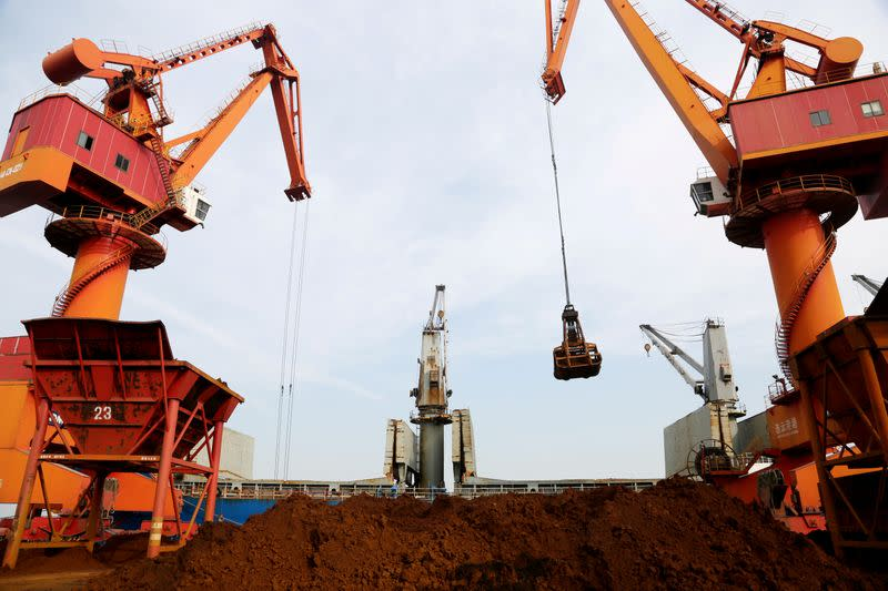 FILE PHOTO: Cranes unload imported iron ore from a cargo vessel at a port in Lianyungang, Jiangsu