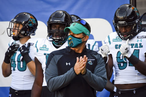 FILE - In this Saturday, Oct. 31, 2020, file photo, Coastal Carolina head coach Jamey Chadwell waits to lead his team onto the field before an NCAA football game against Georgia State in Atlanta. An unusual college football season has produced some unexpected unbeaten teams dotting the AP Top 25 with about a month left. Led by No. 7 Cincinnati and No. 8 BYU, five teams from outside the Power Five conferences have yet to lose. (AP Photo/John Amis, File)