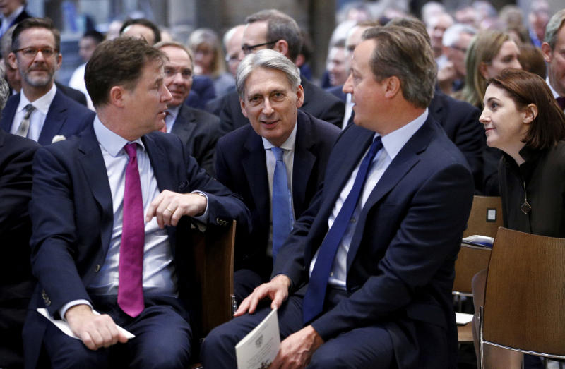 British Chancellor of the Exchequer Philip Hammond , centre, talks with former Deputy Prime Minister Nick Clegg and former Prime Minister David Cameron, in Westminster Abbey during a service of thanksgiving for the life and work of former Cabinet Secretary Jeremy Heywood, in London, Thursday June 20, 2019. (Henry Nicholls/Pool Photo via AP)