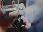 A man passes an advert on a retail premises in London, Tuesday, Oct. 27, 2020. The British government is sticking to its strategy of tiered, regional restrictions to combat COVID-19 amid mounting political and scientific pressure for stronger nationwide measures to prevent the pandemic from spiralling out of control. (AP Photo/Kirsty Wigglesworth)