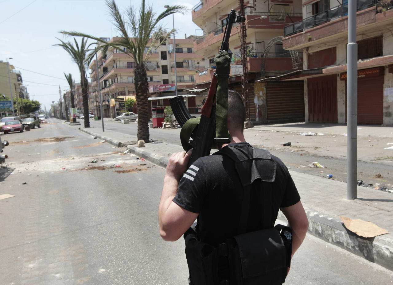 A Sunni gunman stands at Syria Street which divides the Sunni and Alawite areas, in the northern port city of Tripoli, Lebanon, Sunday May 13, 2012. Gunfire broke out in the city Saturday and continued through the night primarily between a neighborhood populated by Sunni Muslims who hate Syrian President Bashar Assad and another area with many Assad backers from his Alawite sect. Lebanon's national news agency NNA said one soldier was shot dead by a sniper in the city early Sunday. Another man was found dead on the side of a road while a third died after a shell landed in a residential neighborhood. (AP Photo/Hussein Malla)