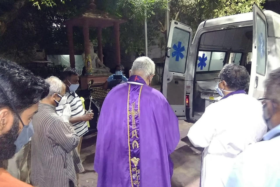 In this April 18, 2021, photo provided by the Rev. Cedric Prakash, priests pray over the body of the Rev. Jerry Sequeira before his cremation in Ahmedabad, India. Sequeira is one of more than 500 Catholic priests and nuns who have died from COVID-19 in India, according to the Rev. Suresh Mathew, a priest at Holy Redeemer's Church in New Delhi and the editor of the church-run Indian Currents magazine. (Cedric Prakash via AP)