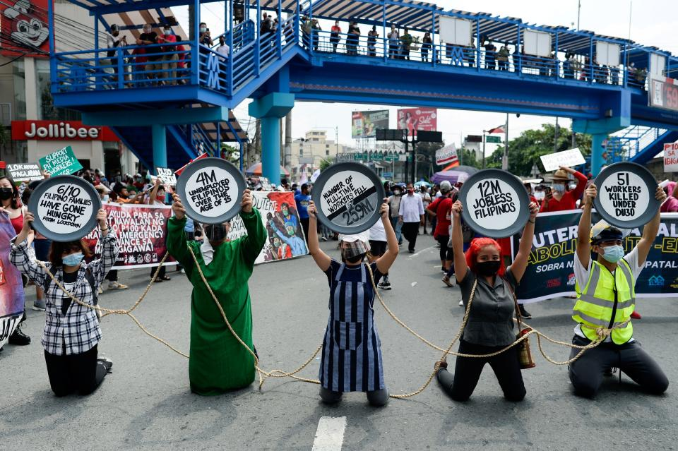Protesters kneel as they raise placards during a Labor Day protest, in Quezon City, Metro Manila, Philippines, May 1, 2021. REUTERS/Lisa Marie David