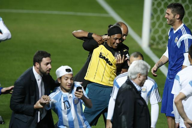 A security guards grab two fans who invaded the pitch, one resembling Brazilian soccer fan Ronaldinho, top, at the end of the training session of the Argentine team at Independencia Stadium in Belo Horizonte, Brazil, Wednesday, June 11, 2014. Argentina will play in group F of the Brazil 2014 soccer World Cup. (AP Photo/Victor R. Caivano)