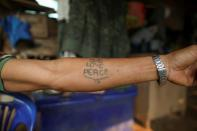 Izzie, 49, former Karenni Army (KNPP) soldier shows his tattoo in the Kayan village in Mae Hong Son
