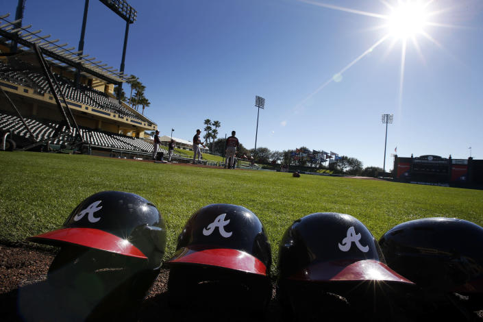 FILE - In this Feb. 18, 2014, file photo, Atlanta Braves batting helmets sits on the field under a shining sun during a spring training baseball workout in Kissimmee, Fla. Major League Baseball revamped its spring training exhibition schedule because of the pandemic, cutting travel for Florida-based teams in an effort to avoid the novel coronavirus, the league announced Friday, Feb. 12, 2021. (AP Photo/Alex Brandon, File)