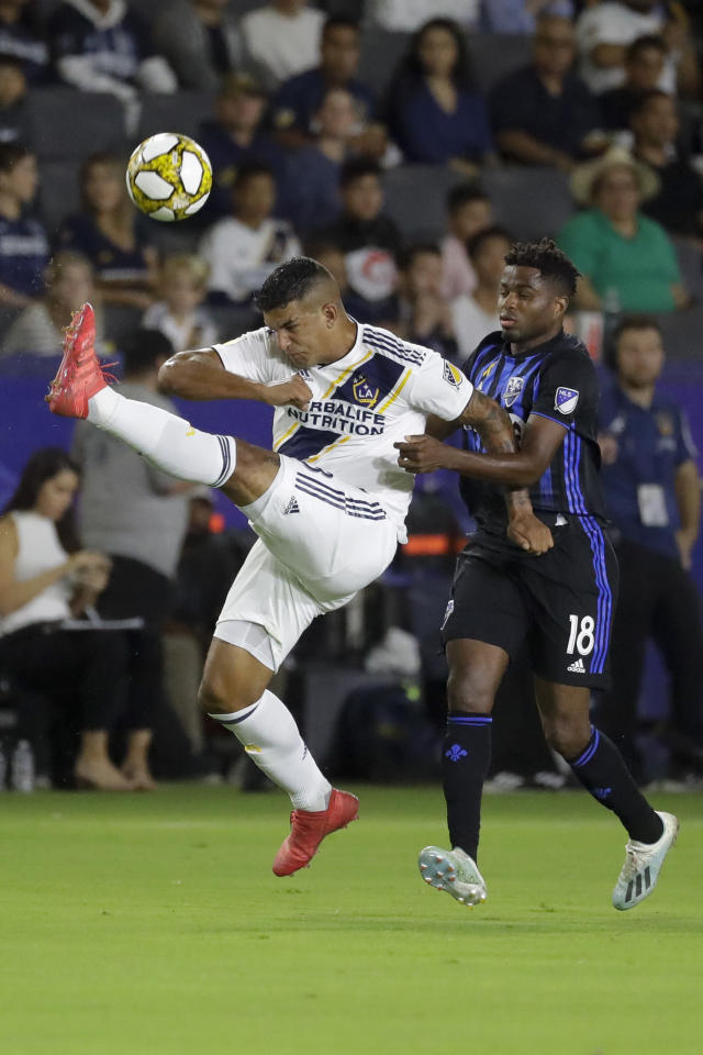LA Galaxy defender Diego Polenta, left, kicks the ball over Montreal Impact forward Orji Okwonkwo during the first half of an MLS soccer match in Carson, Calif., Saturday, Sept. 21, 2019. (AP Photo/Chris Carlson)