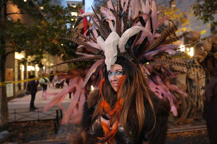A reveler with costume filled with feathers awaits the start of the Halloween Parade in New York City. (Photo: Gordon Donovan/Yahoo News)