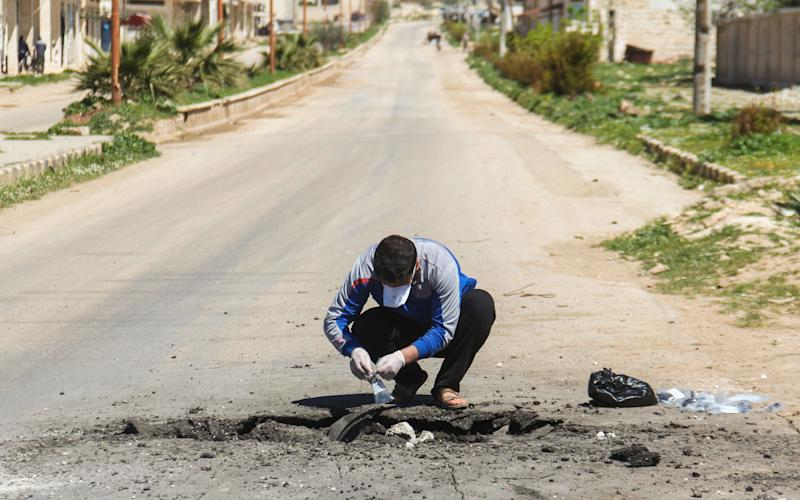 A Syrian man collects samples from the site of a suspected toxic gas attack in Khan Sheikhun, in Syrias northwestern Idlib province, on April 5, 2017 - Credit: AFP