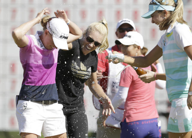 Stacy Lewis, left, is sprayed by Lexi Thompson, right, and Natalie Gulbis after winning the North Texas LPGA Shootout golf tournament at Las Colinas Country Club in Irving, Texas, Sunday, May 4, 2014. (AP Photo/LM Otero)