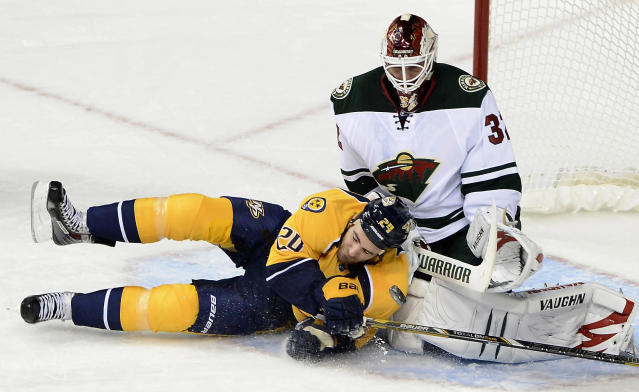 Nashville Predators forward Eric Nystrom, left, collides with Minnesota Wild goalie Niklas Backstrom (32), of Finland, after being slashed, resulting in a penalty shot in the first period of an NHL hockey game on Tuesday, Oct. 8, 2013, in Nashville, Tenn. (AP Photo/Mark Zaleski)