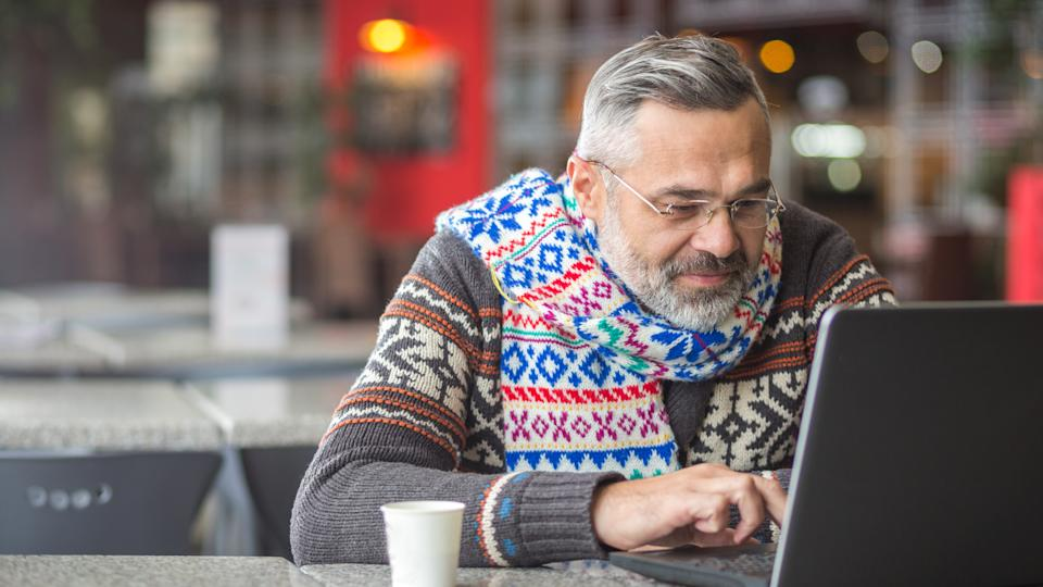 Man wearing autumn or winter clothes, scarf sitting in a cafe working using laptop