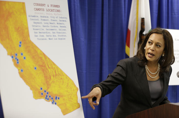 FILE - In this Mar. 24, 2016, file photo, California Attorney General Kamala Harris points to a display showing the location of Corinthian Colleges located in California during a news conference in San Francisco. On Thursday, March 24, 2016, a San Francisco Superior Court judge awarded the state a nearly $1.2 billion default judgment against Corinthian Colleges Inc., the bankrupt operator of for-profit colleges. (AP Photo/Eric Risberg, File)
