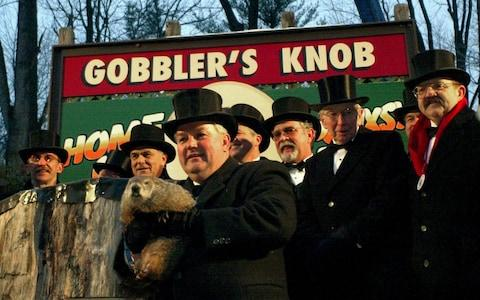 """Groundhog handler Bill Deeley and members of the """"Inner Circle"""" pose for photos with groundhog Punxsutawney Phil on Groundhog Day 2003 - Credit: Archie Carpenter/Getty Images"""