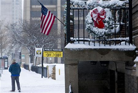 A person walks down a snow-covered sidewalk, as a winter storm moves across the midwest, in Milwaukee, Wisconsin December, 22, 2013. REUTERS/Darren Hauck