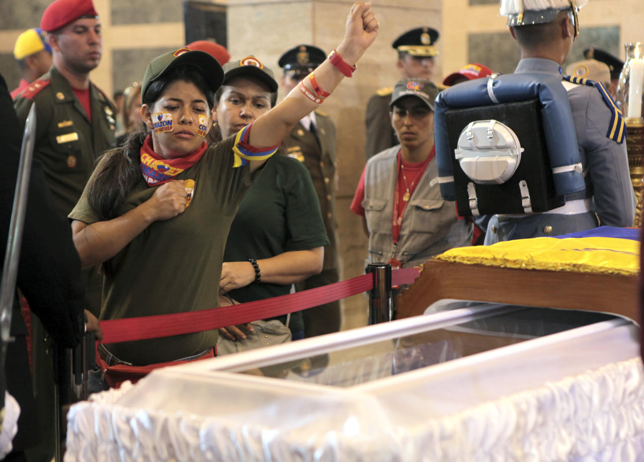 In this photo released by Miraflores Press Office, a woman pays her respects, placing a hand on her heart and saluting, before she files past the glass-topped casket containing the remains of Venezuela's late President Hugo Chavez at the military academy, where he started his army career, in Caracas, Thursday, March 7, 2013. Battling an unspecified cancer, Chavez died Tuesday. His flag-draped coffin lies in state at the military academy as a mile-long line of mourners come to pay homage. (AP Photo/Miraflores Presidential Press Office)