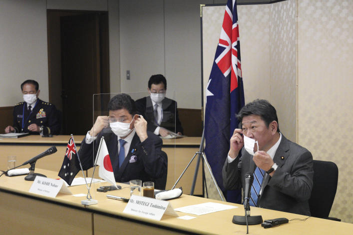 Japanese Foreign Minister Toshimitsu Motegi, right, and Defense Minister Nobuo Kishi, left, remove their protective masks as they attend a video conference with Australian Foreign Minister Marise Payne and Australian Defense Minister Peter Dutton, not in picture, at Foreign Ministry in Tokyo during their two-plus-two ministerial meeting Wednesday, June 9, 2021, in Tokyo. (AP Photo/Eugene Hoshiko, Pool)