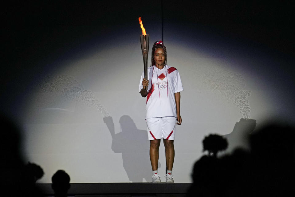 FILE - In this July 23, 2021, file photo, Japan's Naomi Osaka holds the Olympic torch during the opening ceremony in the Olympic Stadium at the 2020 Summer Olympics in Tokyo, Japan. The racial diversity Japan showcased at the Olympic opening ceremony also highlights its lack in Japanese society. (AP Photo/Natacha Pisarenko, File)
