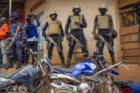 Security forces stand outside a polling station in Kampala, Uganda, Thursday, Jan. 14, 2021. Ugandans are voting in a presidential election tainted by widespread violence that some fear could escalate as security forces try to stop supporters of leading opposition challenger Bobi Wine from monitoring polling stations. (AP Photo/Jerome Delay)