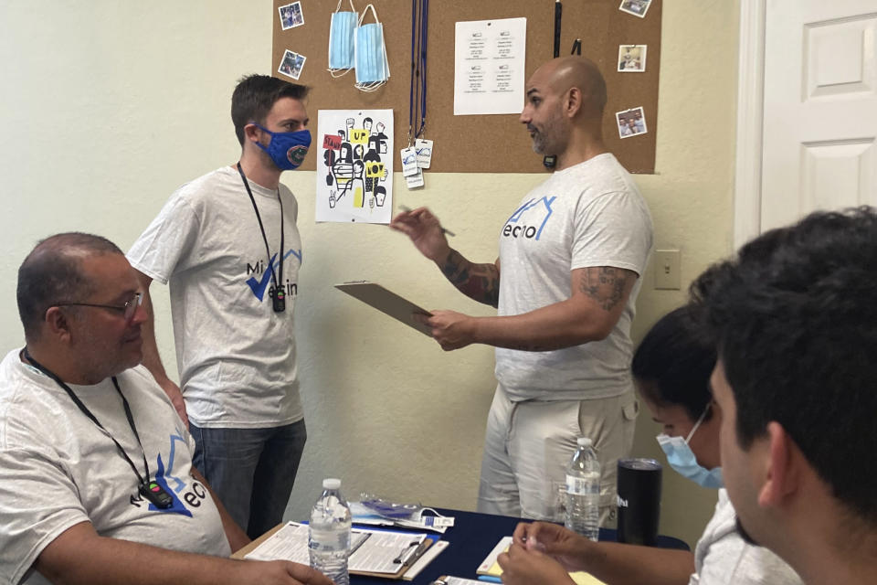 Alex Berrios, right, co-founder of the nonprofit Mi Vecino, coaches newly hired staff member Colby Snaidman, right, on how best to approach people and convince them to register to vote on Thursday, June 24, 2021, in Kissimmee, Fla. Mi Vecino, and other advocacy organizations affiliated with Democrats, are trying to engage Latino voters earlier and build lasting relationships after Republicans gained ground with voters in some Latino communities during last year's presidential and congressional races. (AP Photo/Will Weissert)