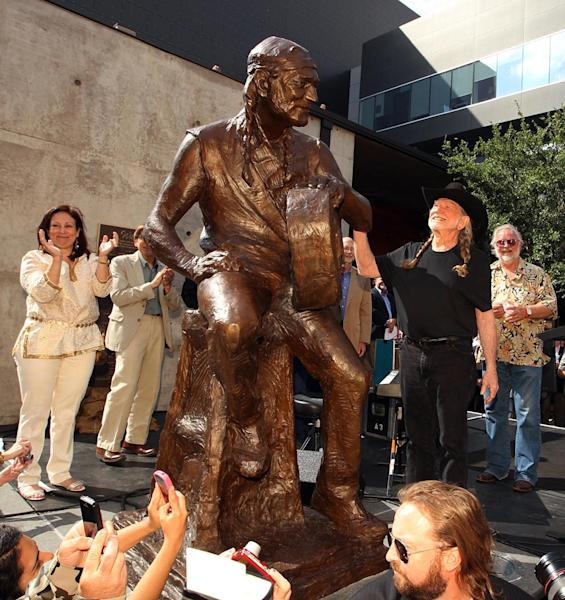 Country singer Willie Nelson looks at his statue during the unveiling of an eight-foot statue of himself, Friday, April 20, 2012 in Austin, Texas. The privately-funded monument near the new Moody Theater shows Nelson in a relaxed, standing pose and holding his guitar to the side, as if in conversation. (AP Photo/Austin American-Statesman, Jay Janner) MAGS OUT; NO SALES; INTERNET AND TV MUST CREDIT PHOTOGRAPHER AND STATESMAN.COM