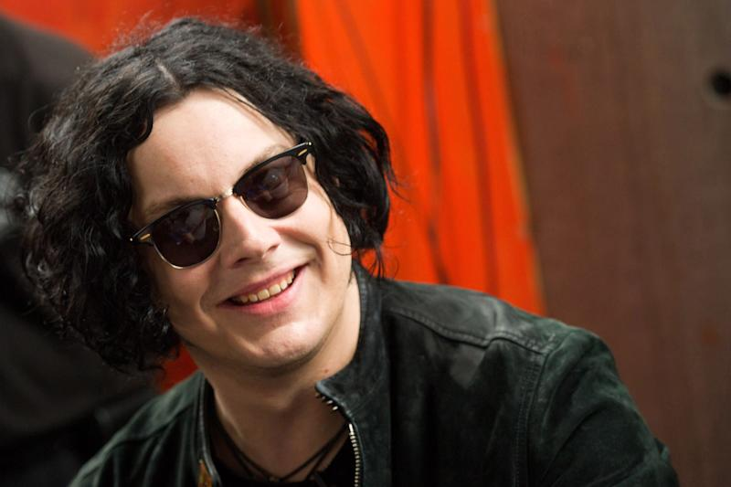 "FILE - In this June 24, 2011 file photo, Jack White signs copies of the record he made with Stephen Colbert in New York. White will kick off the release of his first solo album with a concert streamed live online, to be directed by Gary Oldman. The show will be the first installment of American Express' ""Unstaged"" series, which pairs top musical acts with renown filmmakers. White's concert at New York's Webster Hall will be streamed live April 27, 2012, at 9 p.m. EST on VEVO.  (AP Photo/Charles Sykes, File)"