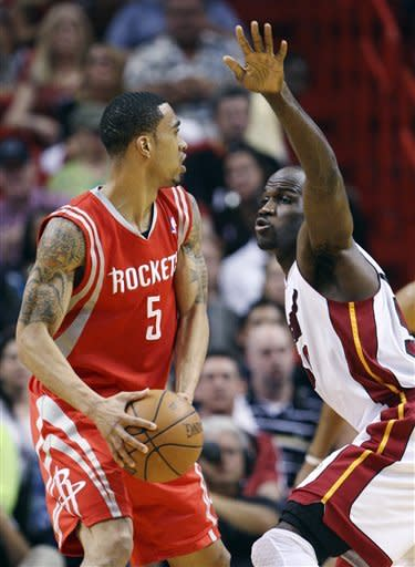 Houston Rockets guard Courtney Lee (5) looks for an open teammate past Miami Heat center Joel Anthony during the first half of an NBA basketball game, Sunday, April 22, 2012, in Miami. (AP Photo/Wilfredo Lee)