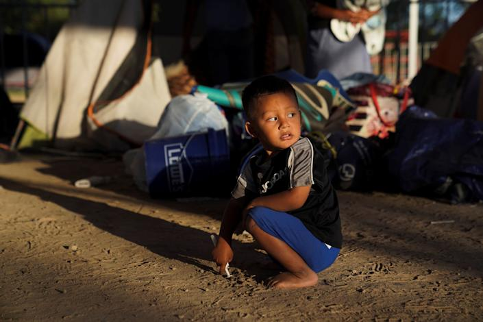 Elias, 2, a Honduran asylum-seeking child, plays near the tent where he lives after being relocated from the plaza near the Gateway International Bridge in Matamoros, Mexico, on Dec. 7, 2019. (Photo: Veronica Cardenas / Reuters)