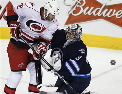 Carolina Hurricanes' Nicolas Blanchard (72) cannot knock a loose puck past Winnipeg Jets goaltender Ondrej Pavelec (31) during the first period of their NHL hockey game in Winnipeg, Manitoba, Thursday, April 18, 2013. (AP Photo/The Canadian Press, John Woods)