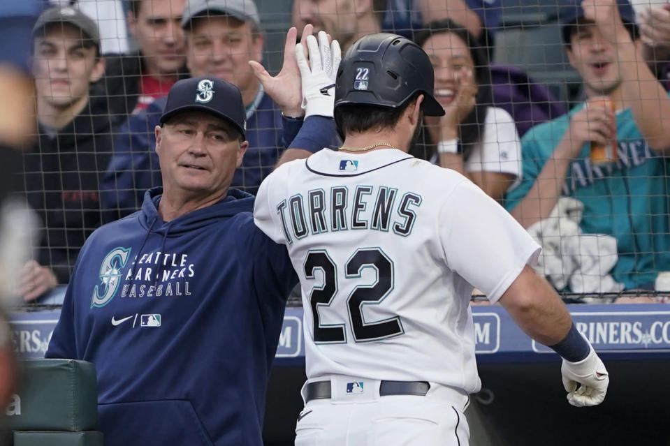 Seattle Mariners manager Scott Servais, left, greets Luis Torrens after Torrens hit a solo home run against the Tampa Bay Rays during the fifth inning of a baseball game Thursday, June 17, 2021, in Seattle. (AP Photo/Ted S. Warren)