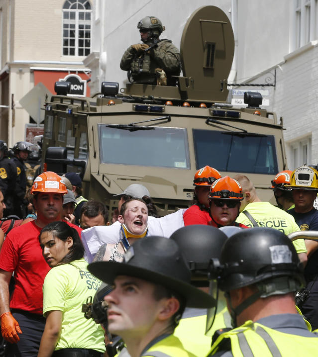 <p>Rescue personnel help injured people after a car ran into a large group of protesters after an white nationalist rally in Charlottesville, Va., Saturday, Aug. 12, 2017. (Photo: Steve Helber/AP) </p>