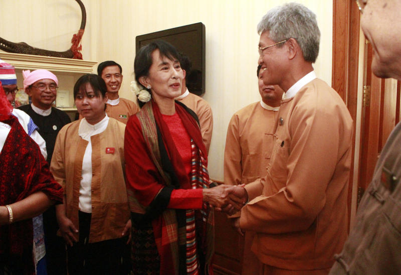 Myanmar pro-democracy leader Aung San Suu Kyi, center left, shakes hand with an unidentified Myanmar parliament member after their meeting at a hotel in Naypyitaw, Myanmar, Tuesday, March. 6, 2012. (AP Photo/Khin Maung Win, Pool)