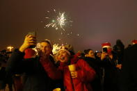Passengers of a party bus celebrate New Year after driving through Moscow, Russia, Friday, Jan. 1, 2021. While restaurants and other entertainment venues close its doors across the country at 23:00, Muscovites look for ways to bend the coronavirus restrictions. One of them is a party bus whose owners offer to spend the New Year night touring around the city and having drinks with other strangers. (AP Photo/Alexander Zemlianichenko Jr)