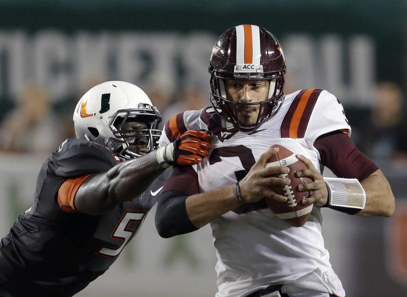 Virginia Tech quarterback Logan Thomas, right, shakes off a tackle by Miami defensive lineman Shayon Green during the first half of an NCAA college football game, Saturday, Nov. 9, 2013, in Miami Gardens, Fla. (AP Photo/Wilfredo Lee)