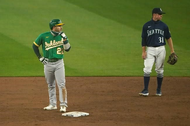 Minor tosses 2-hitter, A's manage split with Mariners