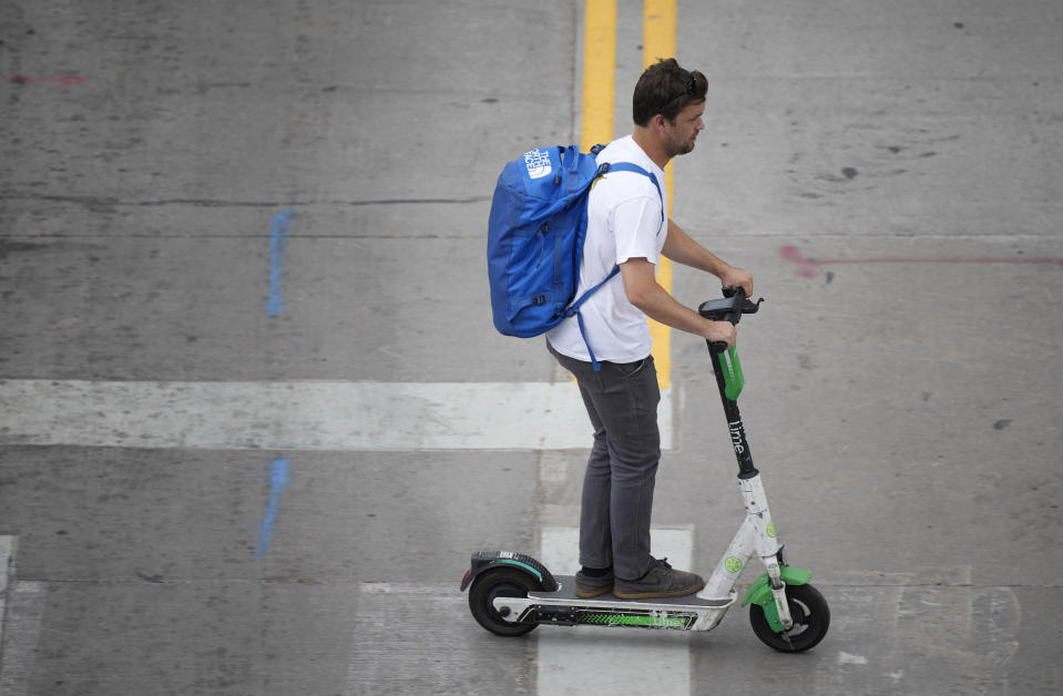 As temperatures soar into the triple digits for the third straight day, a man uses a scooter to move along 20th Street Thursday, June 17, 2021, in Denver. (AP Photo/David Zalubowski)