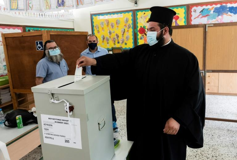 A Greek-Cypriot priest cast his ballot at a polling station in Nicosia on May 30, 2021 for parliamentary elections