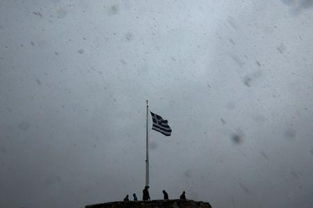 A Greek national flag flutters atop the Athens Acropolis hill as tourists take photos during a snowstorm