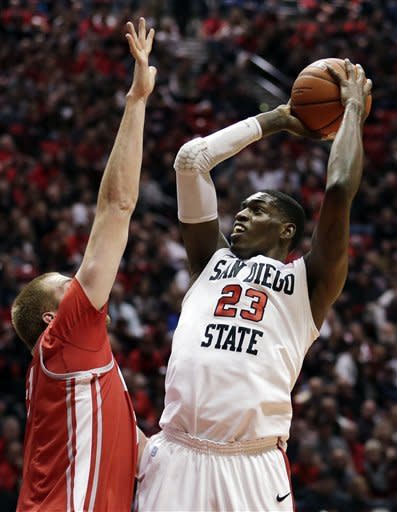 San Diego State's Deshawn Stephens, right, shoots as New Mexico's Alex Kirk defends in the first half during an NCAA college basketball game Saturday, Jan. 26, 2013, in San Diego. (AP Photo/Gregory Bull)