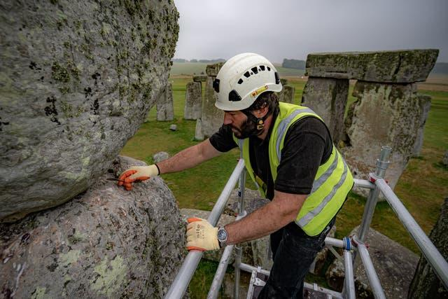 Conservator James Preston uses a pointing spoon atop scaffold erected inside the stone circle at Stonehenge (Ben Birchall/PA)