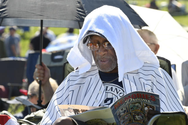 Mariano Rivera fan Eugenino Edwards, of New York, uses a towel to keep cool before the National Baseball Hall of Fame induction ceremony at the Clark Sports Center, Sunday, July 21, 2019, in Cooperstown, N.Y. (AP Photo/Hans Pennink)