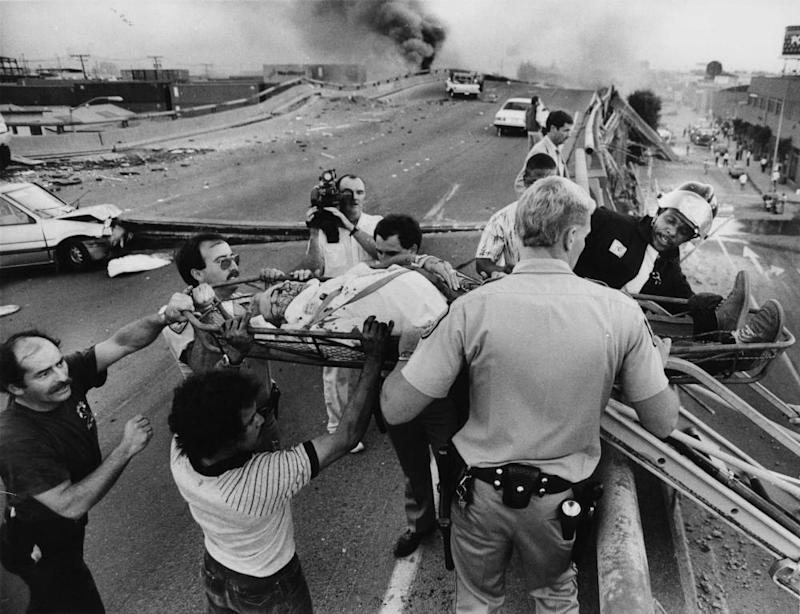 Officials and others evacuate a man, Erick Carlson, from the Cypress section of Highway 17, now called Interstate 880, in Oakland, California, following the Loma Prieta earthquake.