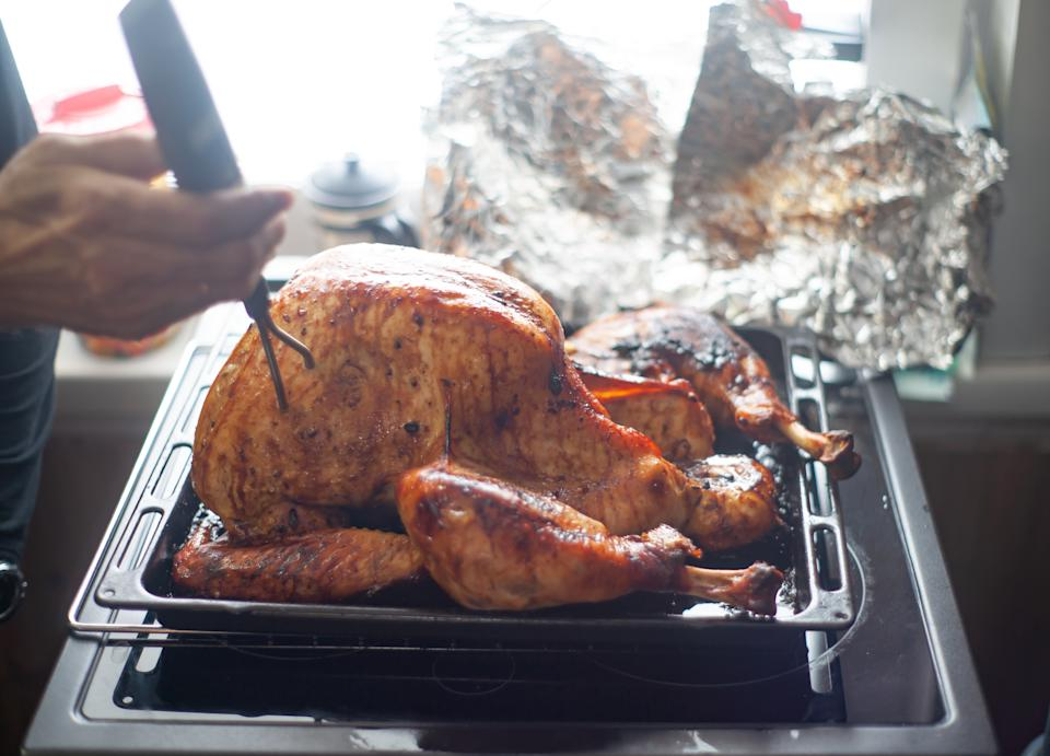 Person check the internal temperature of a roasted turkey.