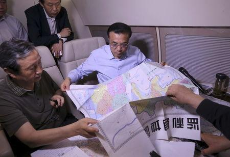 China's Premier Li Keqiang (R) looks at a map as he discusses with experts on a rescue plan, on his plane en route to the site where a ship sank in the Jianli section of Yangtze River, Hubei province, China, June 2, 2015. REUTERS/cnsphoto