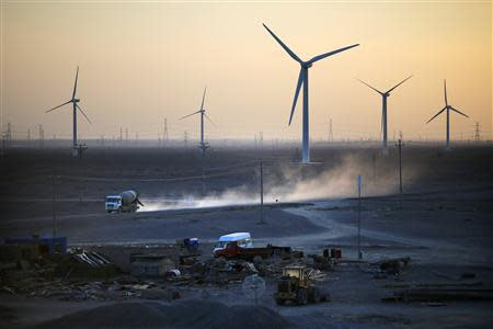 A construction site is seen near wind turbines for generating electricity, at a wind farm in Guazhou, 950km (590 miles) northwest of Lanzhou, Gansu Province September 15, 2013. REUTERS/Carlos Barria