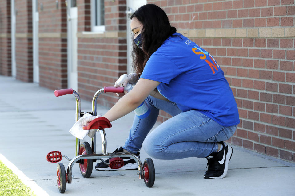 In this May 27, 2020 photo, Alena Kleinman, a worker at the Frederickson KinderCare daycare center in Tacoma, Wash., wears a mask as she cleans a tricycle following use by a class, a task that is repeated several times a day. In a world weary of the coronavirus, many working parents with young children are now struggling with the decision on when or how they'll be comfortable returning to their child care providers. Frederickson KinderCare has been open throughout the pandemic to care for children of essential workers. (AP Photo/Ted S. Warren)