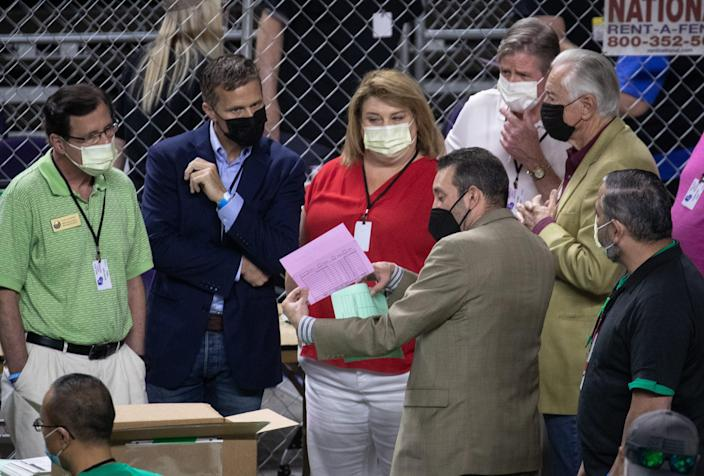 Wisconsin State Representative Janel Brandtjen (center), Eric Greitens (2nd from left) and Wisconsin State Representative Dave Murphy (left) watch as Maricopa County ballots from the 2020 general election are examined and recounted by contractors hired by the Arizona Senate on June 12, 2021, at Arizona Veterans Memorial Coliseum in Phoenix, Ariz.
